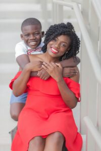A boy with arms wrapped around woman in red dress.