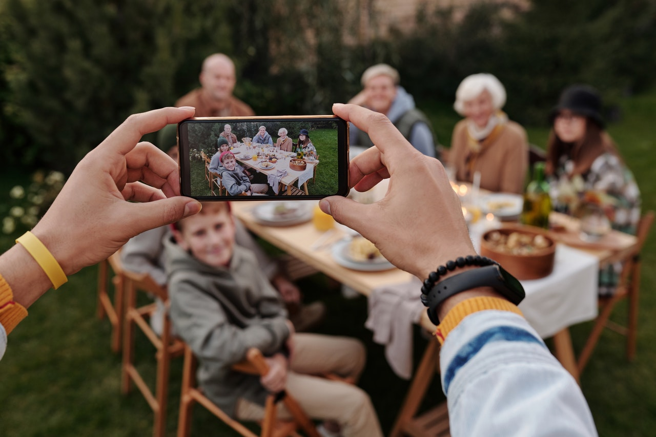 Person holding smartphone, taking picture of people at a table