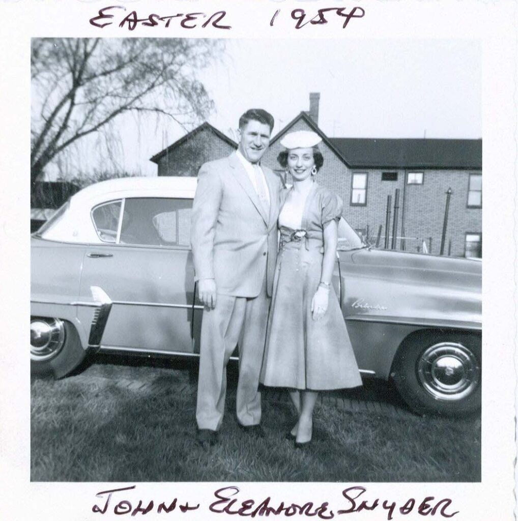Married couple 1954 in front of car and house