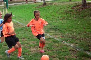 Girls chasing soccer ball