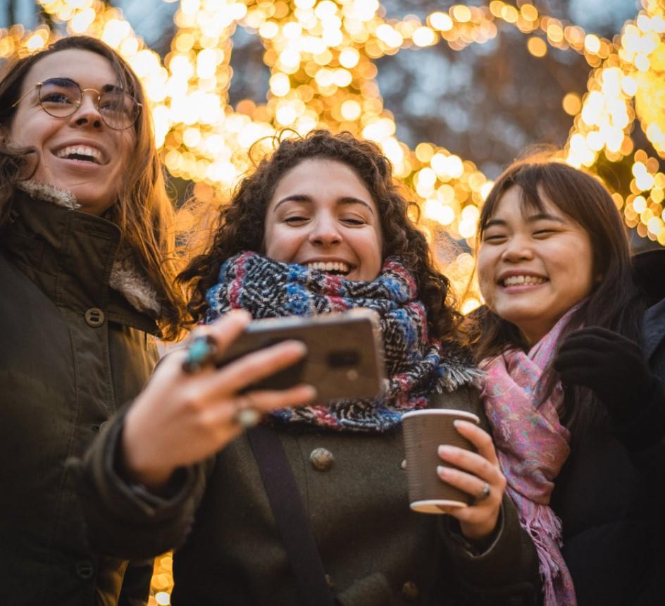 Three women smiling at phone camera