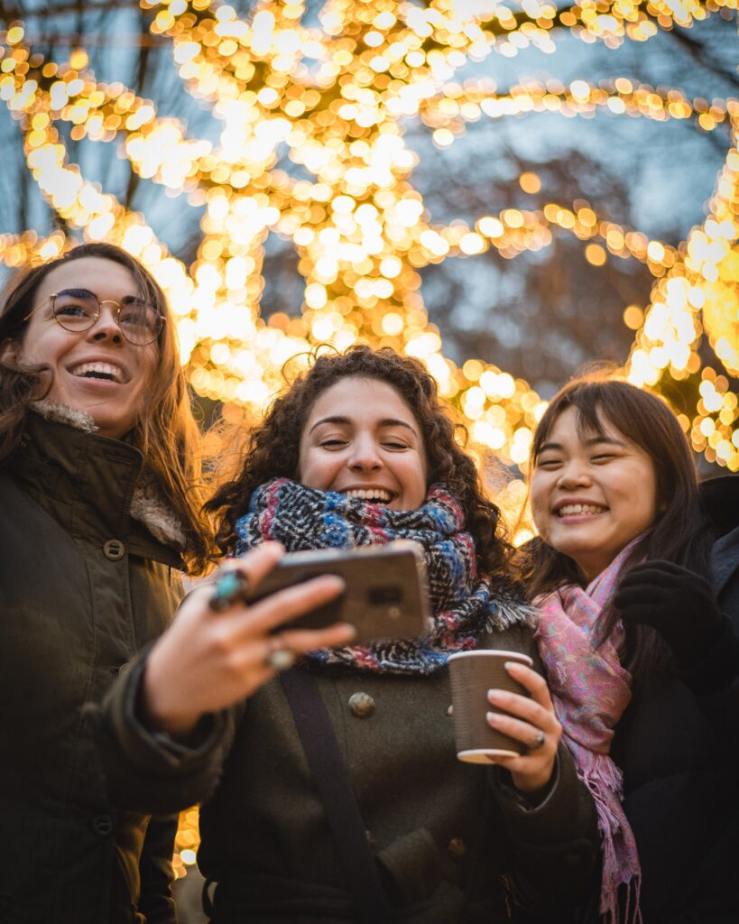 Three women looking at smartphone, smiling