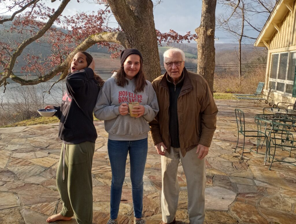Teen girls with grandfather on patio