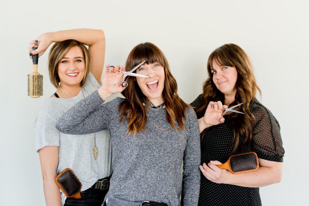 three women with styling scissors and brush
