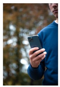 Man outdoors holding iPhone